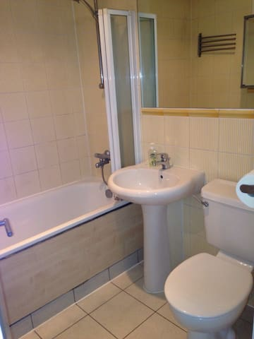 Clean and modern bathroom with shower, towels and towel warmer.