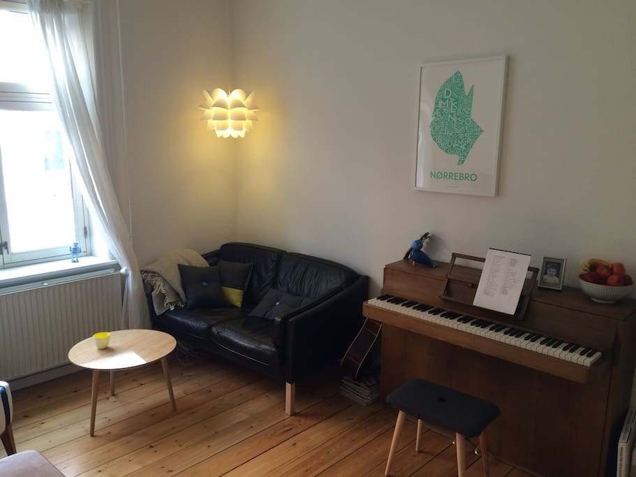 The other side of the living room with a comfortable sofa area and our piano.