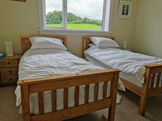 Twin room, single beds with hybrid mattresses. View of rolling hills.