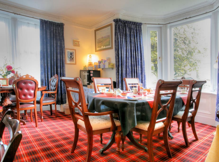 A section of the dining room with tartan carpet.
