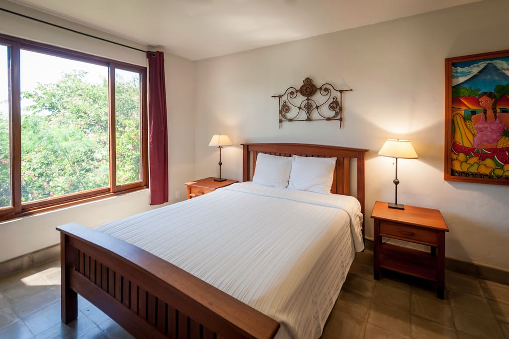 The lower level master suite with comfortable queen bed and local art
