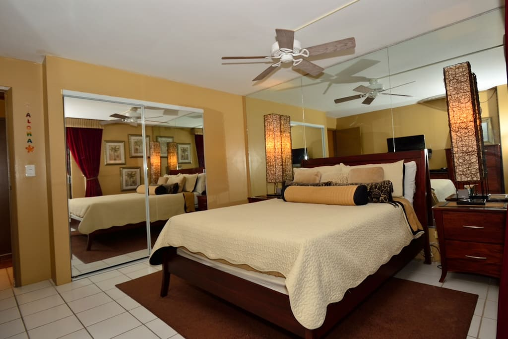 Spacious and beautifully decorated master bedroom with king-sized bed, ceiling fan and lots of storage for hanging and folded clothes