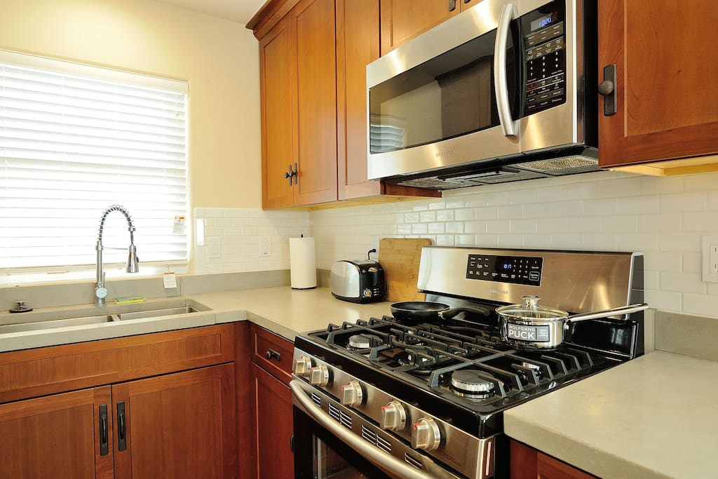 Kitchen with fridge, stove, oven, microwave, and Keurig coffee maker.