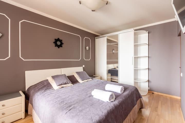 Спальня с большой двуспальная кроватью, телевизором, вместительным шкафом и балконом.