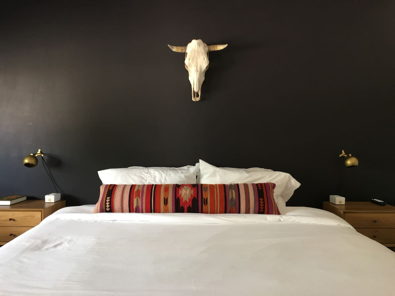 View of the bed and accent wall in Room 04.  This is the same layout you will see in all the king rooms, but with different wall treatments, lights and accents.