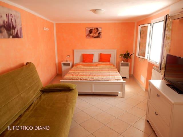 Camera da letto matrimoniale con divano letto e grande televisione