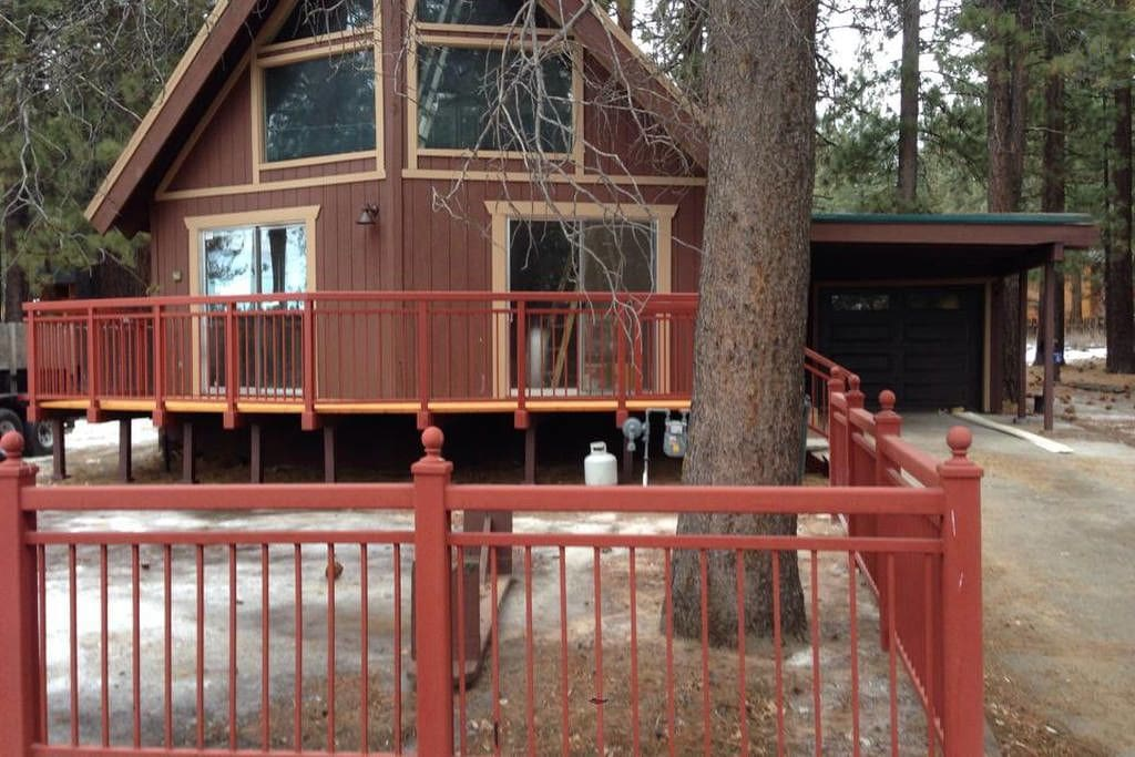 Front of cabin in spring. Double driveways and a garage can accommodate five cars and even an RV.