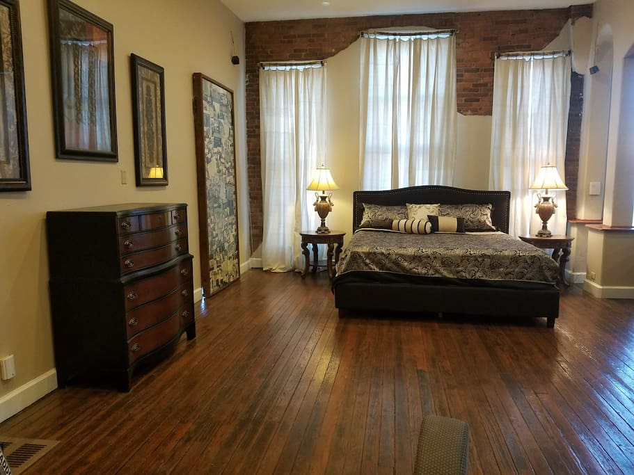 Master bedroom with brand new king size bed and original 1880's hardwood floor.  Dressing room with closet is located through the sliding mural on wall.