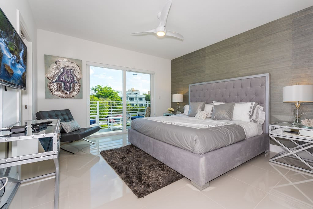 A king bed with tufted headboard, smooth-as-glass tile floors, and balcony access make the master bedroom a pleasant space.