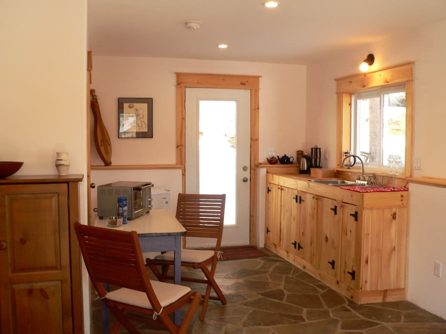 The kitchen corner.  A toaster oven, crock pot, hot plate, kettle and gas bbq with a fitted oven lid and other amenities are available for preparing meals. Guests may share the larger house kitchen for cooking and meals, or create a meal plan to suit them