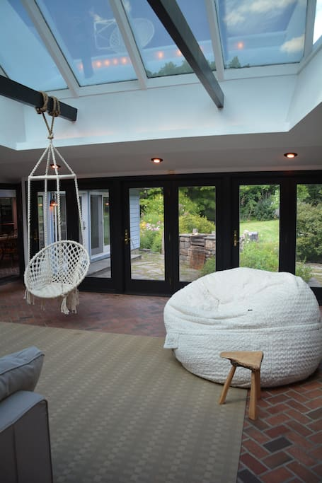 This is the sun room, a super comfortable place for many people to hang. Choose for the huge bean bag, the rope swing chair, or the massive sectional sofa.