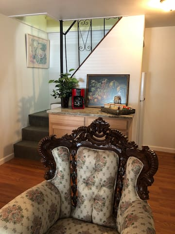 Victorian living room chair, stairs to master bedroom, bathroom & deck..