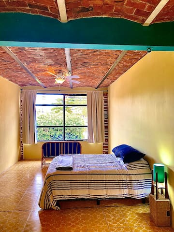 Second bedroom with queen size bed, microfiber sheets, ceiling fan and a sitting area for couples' privacy
