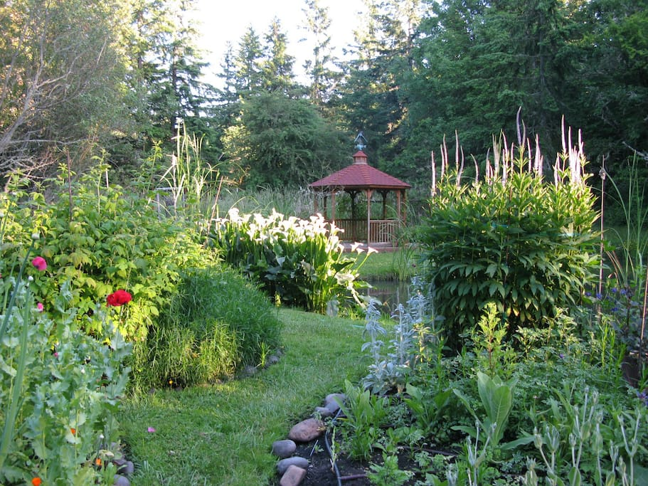 Early summer garden with gazebo in which to relax as you overlook the pond and garden