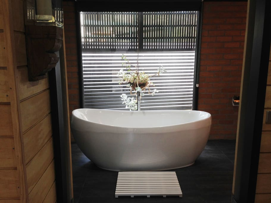 Freestanding tub looks out onto the garden.
