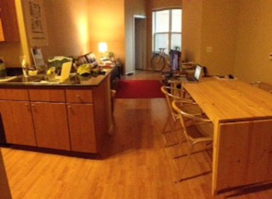 Kitchen is to the right. To the left is a great table for dinning and working.