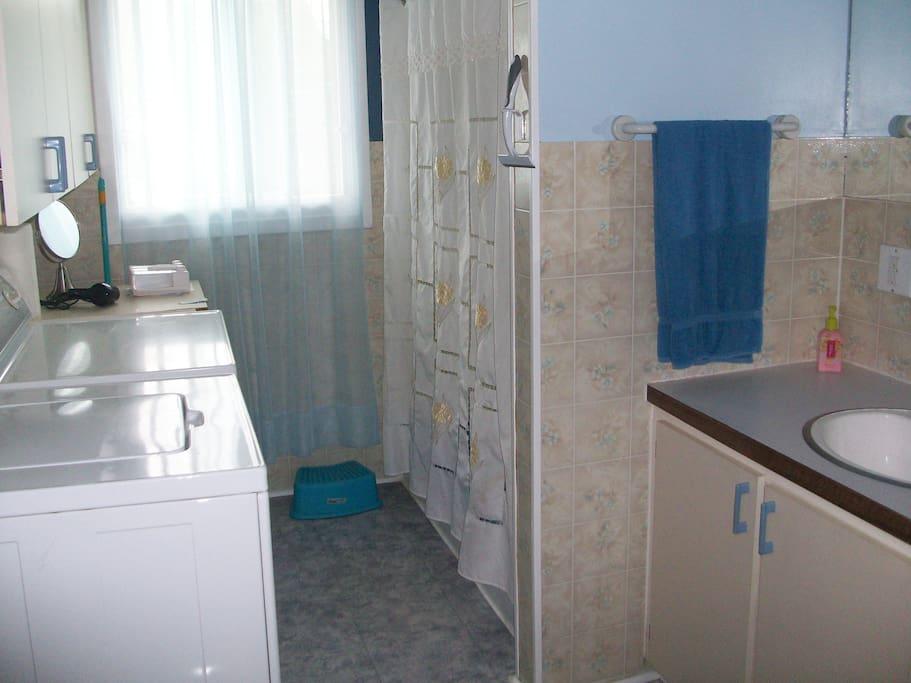 Salle de bain complète avec douche, laveuse et sécheuse.