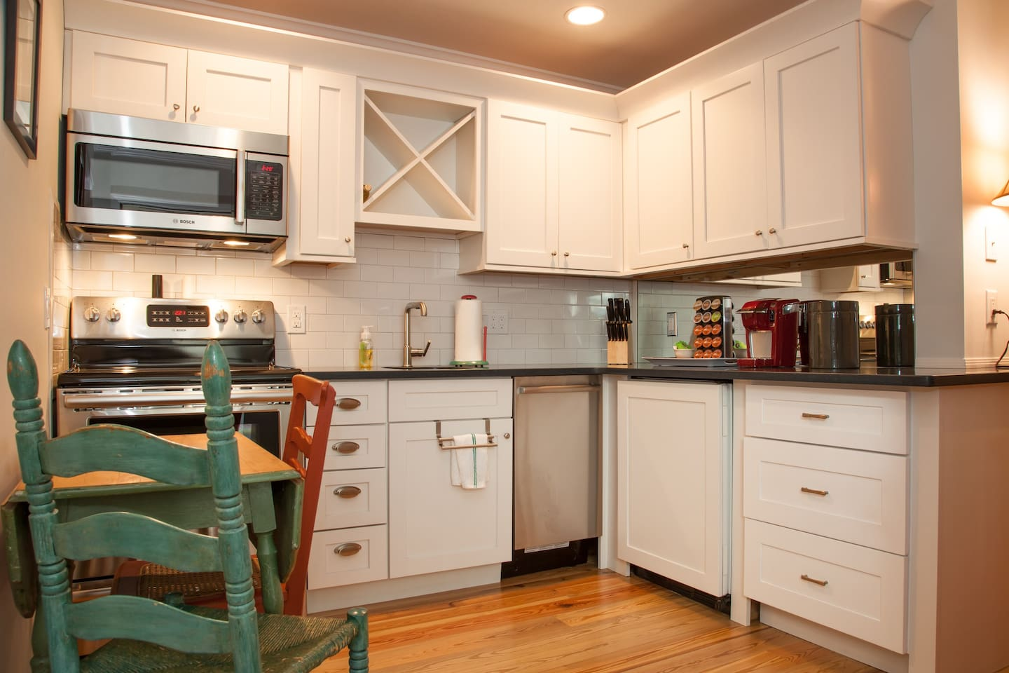 Full kitchen with pots, pans, plates, all types of cups and silverware including a mini fridge and dishwasher.