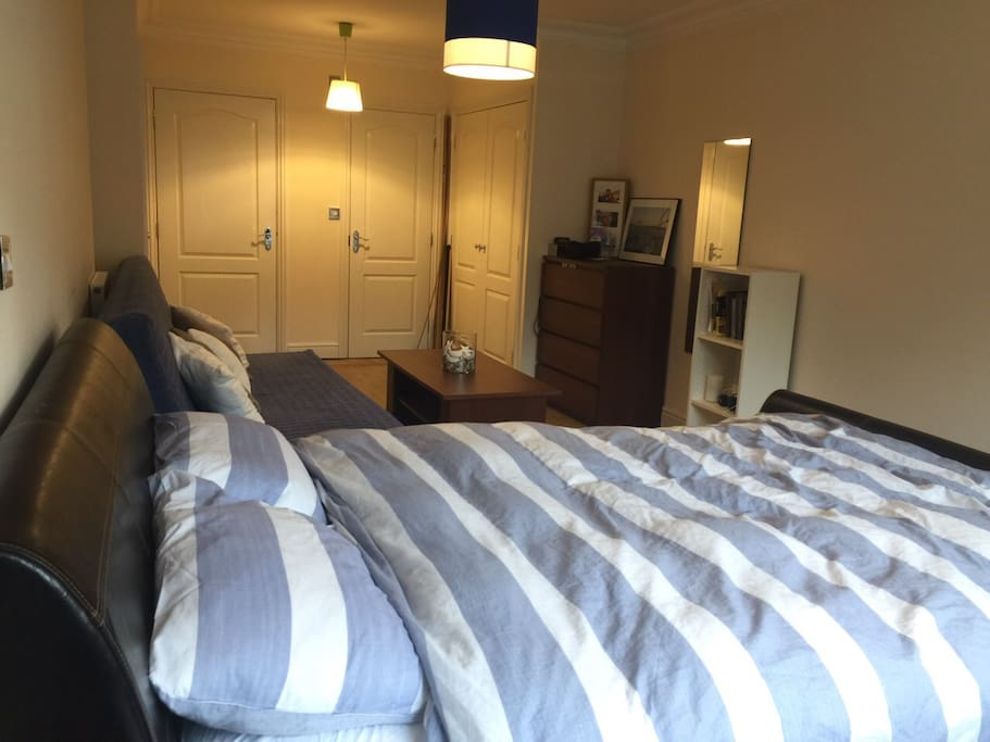 Spacious and Cosy en-suite bedroom with 1 king size bed, a double sofa-bed, and a small study/work desk.