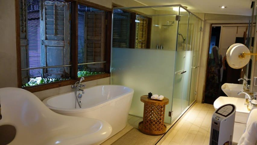 The spacious bathroom with old shutter windows and abandon of day light.