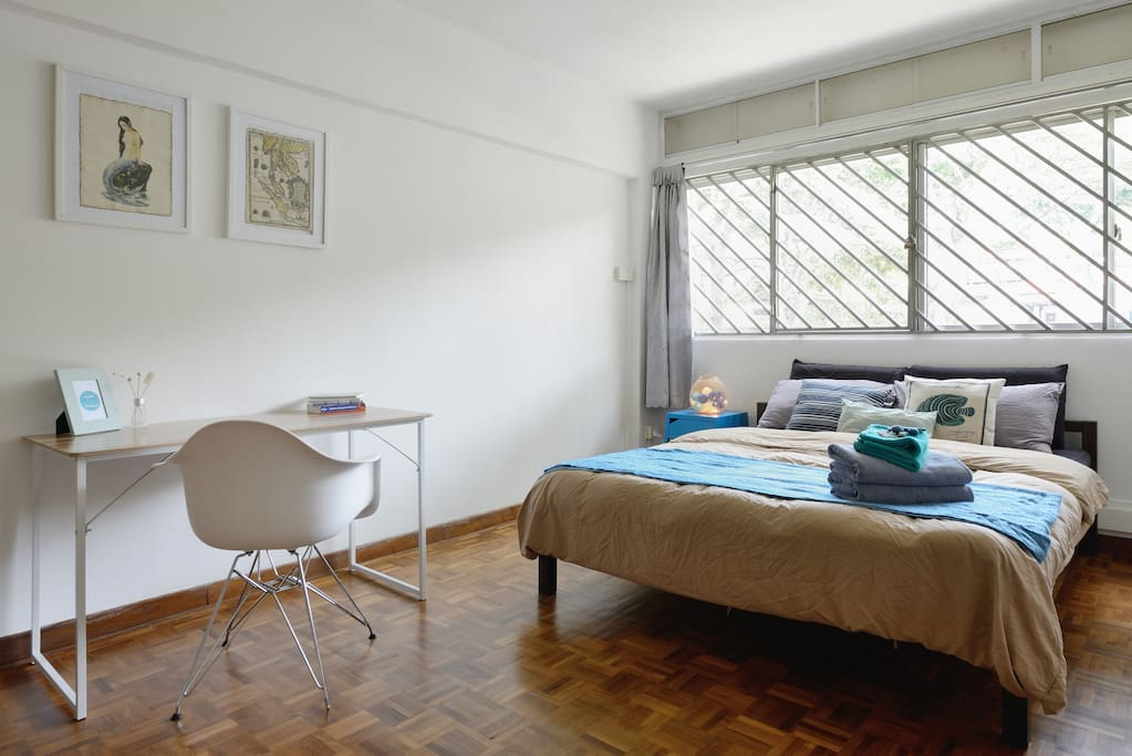 Very spacious bedroom with Queen sized bed, cozy linens and work desk.