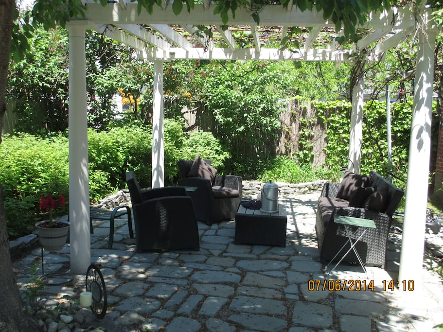 Beautiful outdoor seating area underneath the grapevines, surrounded by raspberry bushes and cherry trees