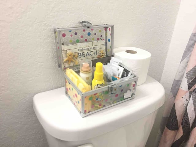 Bathroom is stocked with beauty samples, toilet spray, 1 bottle of dry shampoo, feminine products and an extra roll of toilet paper.