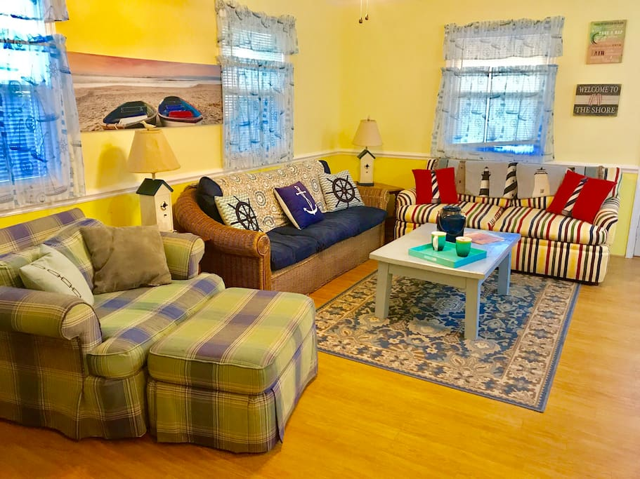 The living room is the spot to get cozy with the beach vibes of our wicker sofa, a sofa bed in colorful stripes, and the comfiest chair we could find!