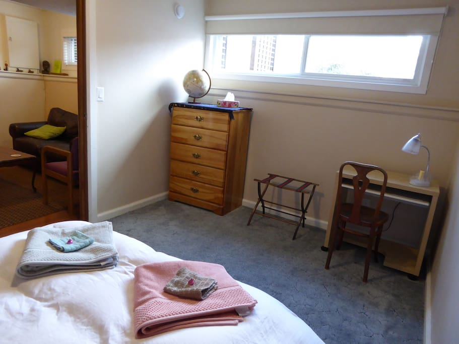 spacious bedroom with desk,full length mirror, suitcase holder, drawers