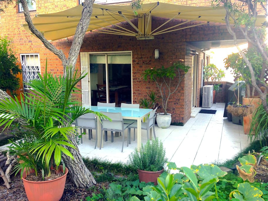 Outdoor paved courtyard BBQ with retractable awning surrounded by garden.