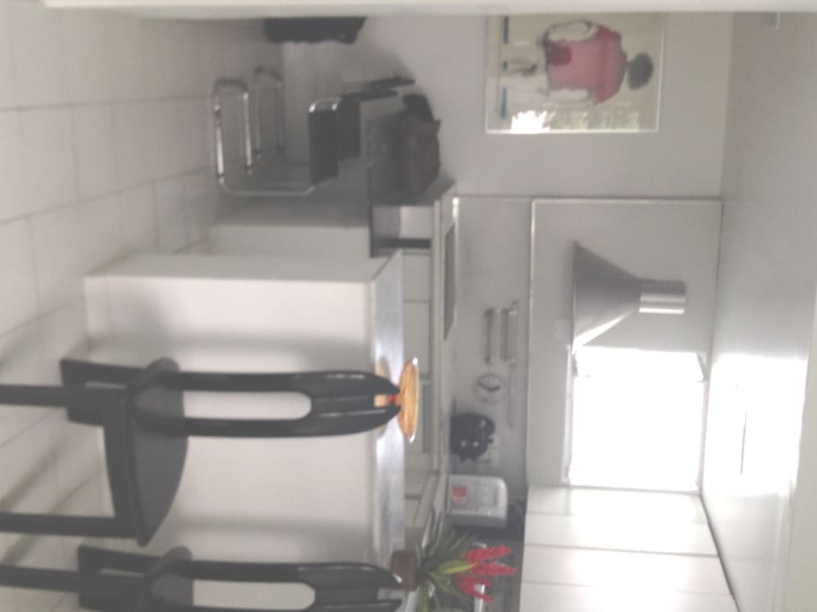 Vista da cozinha da sala com janela, mesa com duas cadeiras. Tem filtro elétrico.