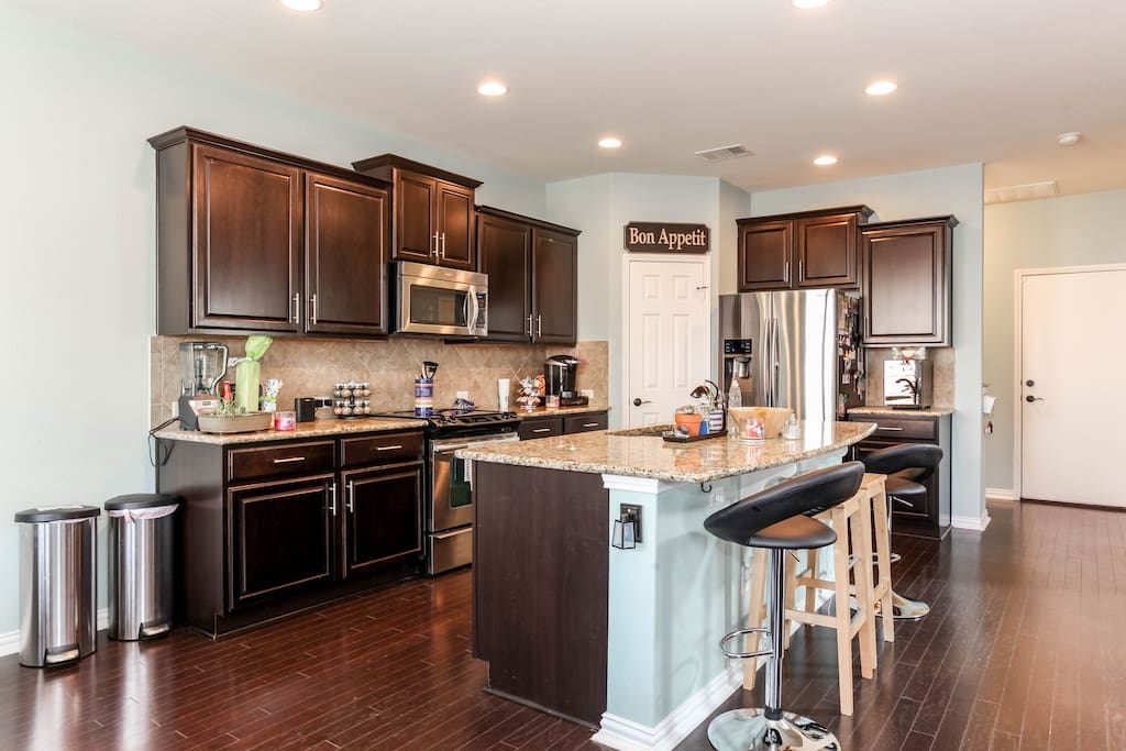Full kitchen access with stainless steel appliances and a large island.