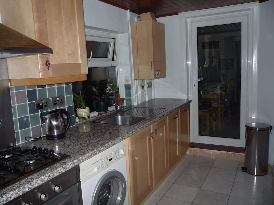 The kitchen, equipped with cooker, fridge, washing machine...