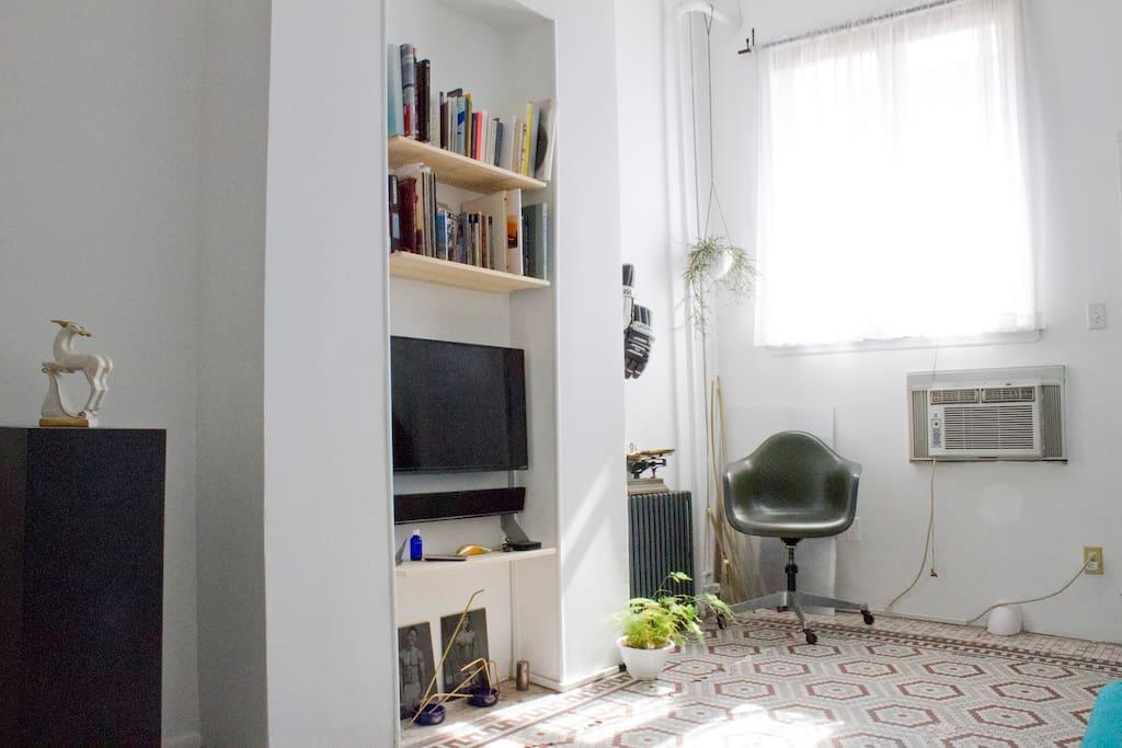 Flatscreen TV, Apple TV, Soundbar, Library.
