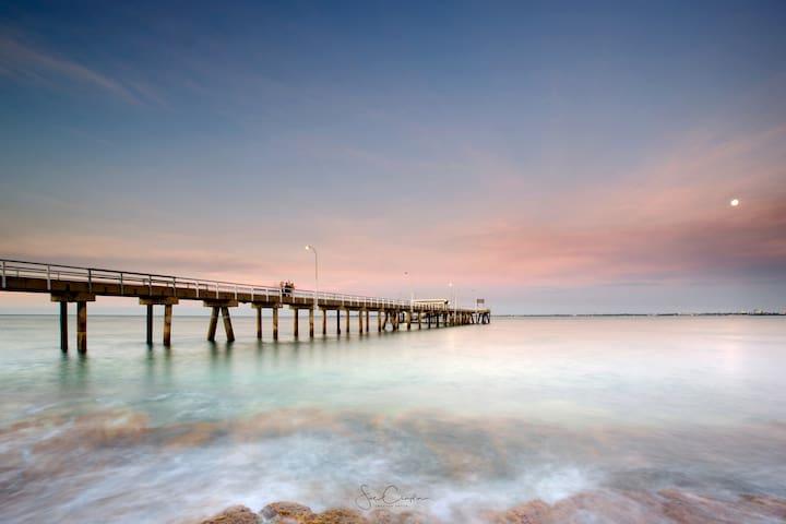 Sunset at Mandorah Jetty.  Beautiful views over Darwin Harbour to the Darwin city lights and skyline