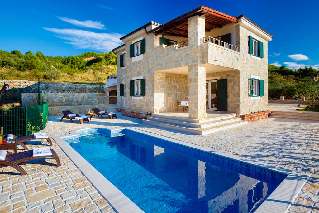 Luxury stone villa Diana made completely from local stone is surrounded by a private pool, outside BBQ, olive trees and Mediterranean plants