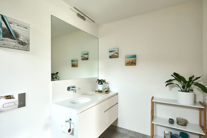 The ensuite has plenty of storage . Shampoo, soap , towels and hairdryer are provided for your use.