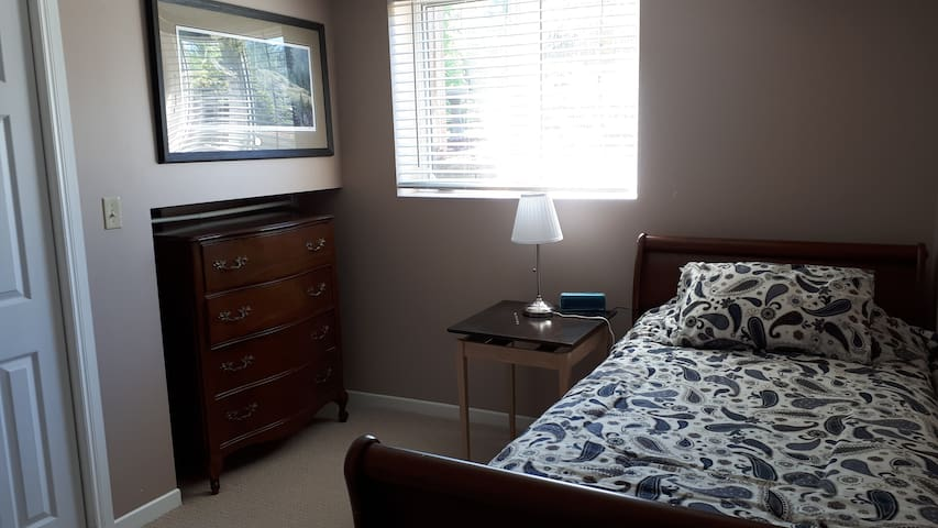 Second bedroom offers a single bed, lots of light, dresser, night stand lamp and alarm clock.