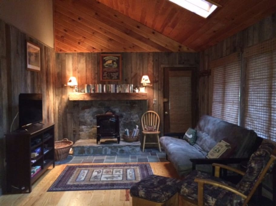 Cozy living room with rustic old barn walls and wood stove