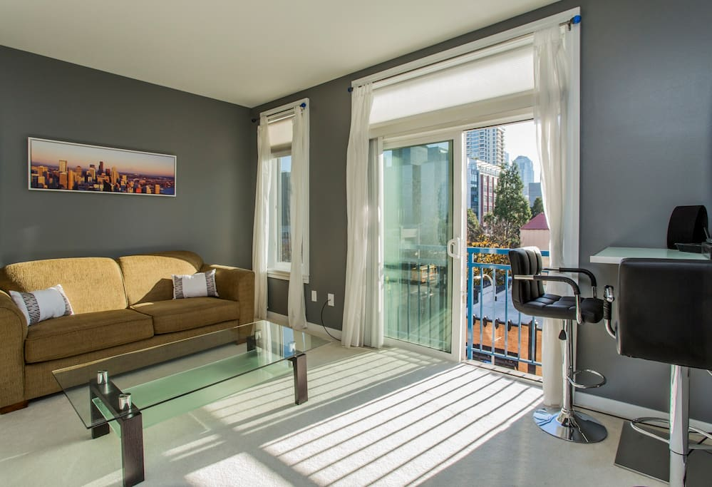 Shade and sheers on windows allow for privacy. Beautiful modern decor throughout.