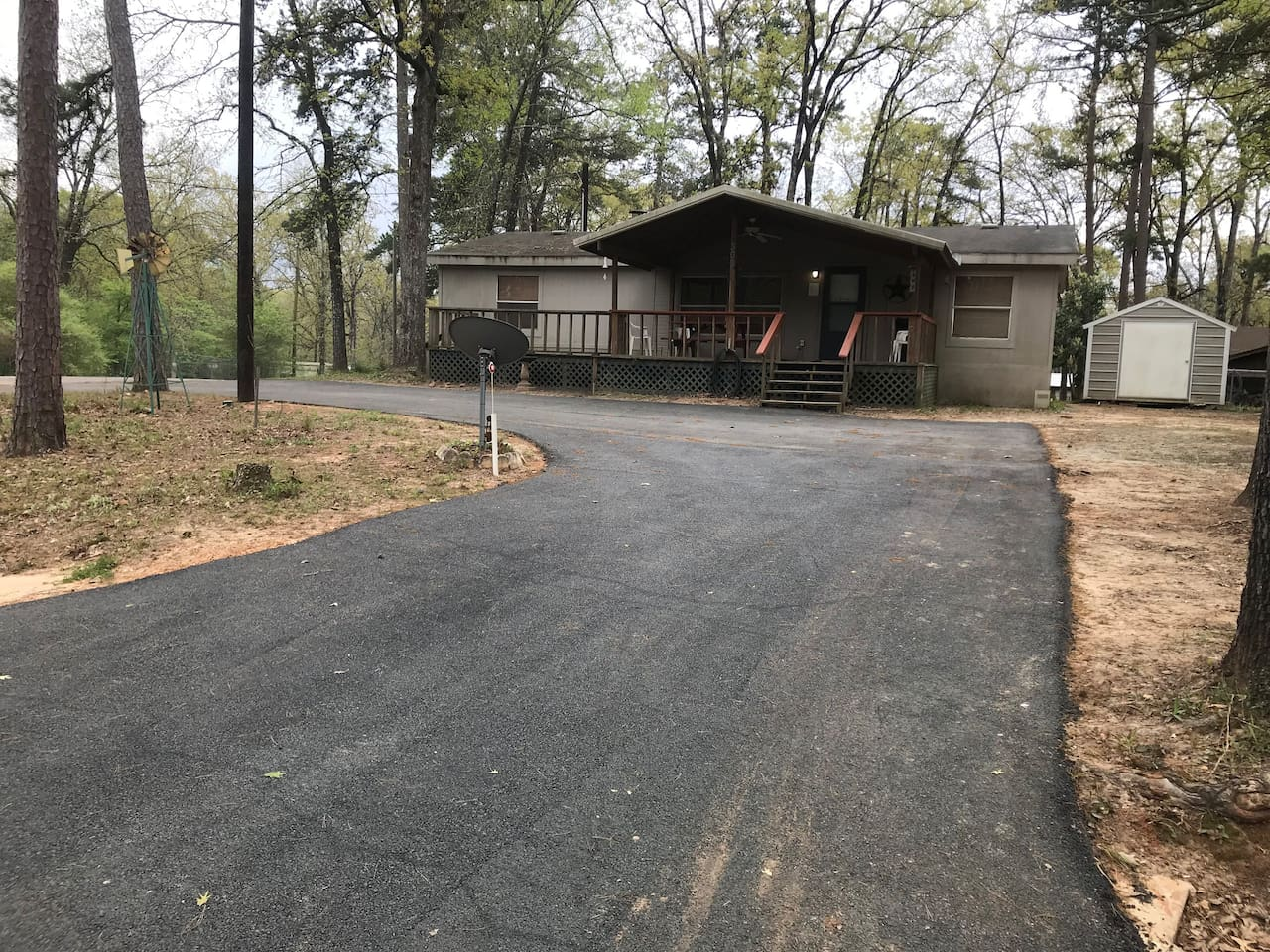 Front of house with paved driveway and large porch with picnic table. Driveway will accommodate bass boats up to 22ft. Outside electric plugs are available.