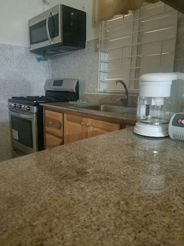 Kitchen appliances: Coffee and Tea maker with microwave and six burner range stove.