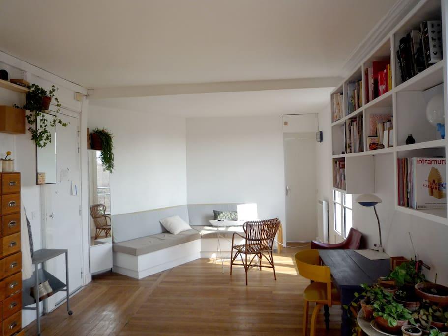 Main room with a large sofa and a desk, two windows with access to the balcony / Pièce principale avec canapé et bureau, deux porte-fenêtres donnent accès au balcon