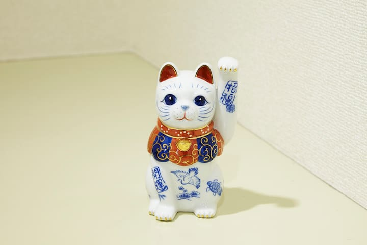 """""""Manekineko"""" is an ornamental beckoning cat. It is usually made of clay which is often found in restaurants and shops in Japan. It is believed to draw visitors and customers."""