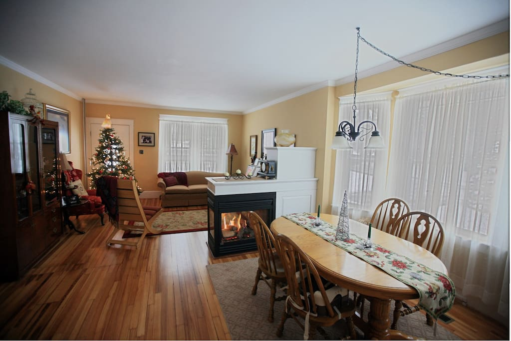 Living room and Dining room. Gas fireplace shows flames on both sides. Dining room in conveniently off of the kitchen.