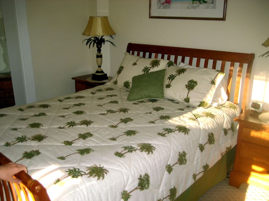 Queen bed with palm tree theme.