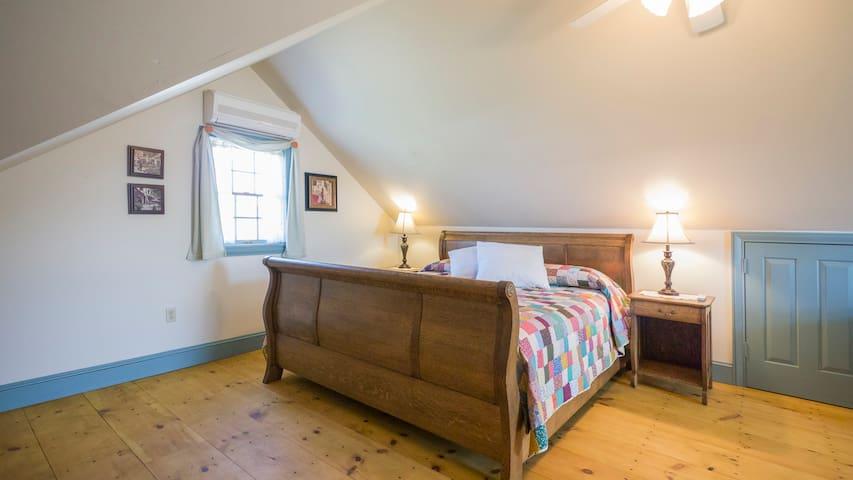King sized bed on pine floor;  Mini split Heat/AC in 2nd floor attic room