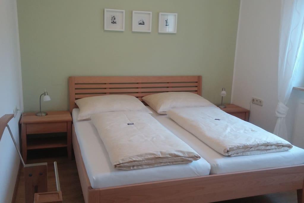 1. Hochwertig ausgestattes Schlafzimmer mit geräumigem Schrank, Nachtkästchen, Leselampen und TV.