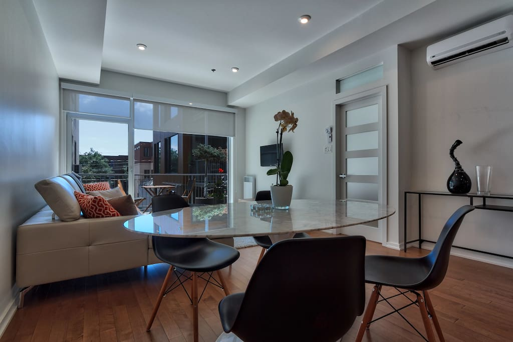 Very bright living room with sofa, TV and space for lunch
