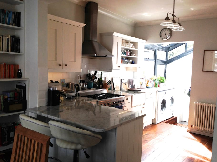 Open-plan, fully equipped kitchen and dining room, with range oven, breakfast bar and 2 bar stools, plus dining table that seats 6; there's also a deep, comfy sofa, well-stocked book shelves and piano. Daylight floods into the side conservatory, which leads to a downstairs toilet.